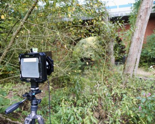 Kamera positioniert. Im Hintergrund die Eisenbahnbrücke.